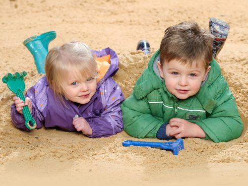 Two toddlers playing outside in the large sand pit at Juniors Day Nursery.