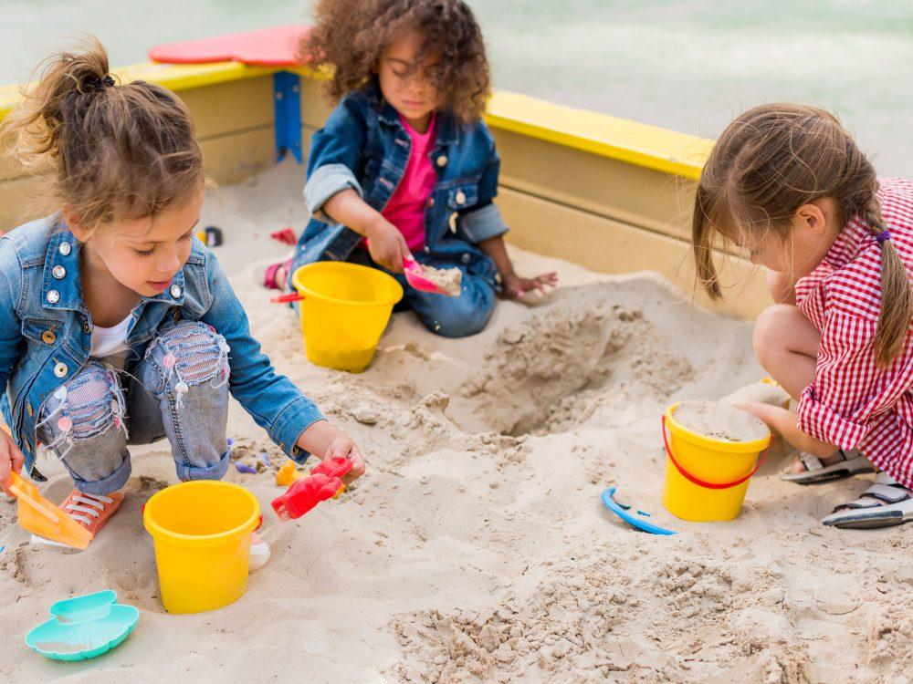 Preschool children playing in the sand pit at Juniors Day Nursery.