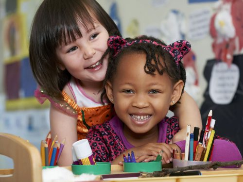 Two pretty girls painting together in the Preschool room at Juniors Day Nursery, Cranbrook.