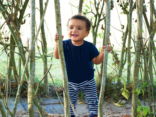 Happy child from the Teenies room playing outside in the garden at Juniors Day Nursery.