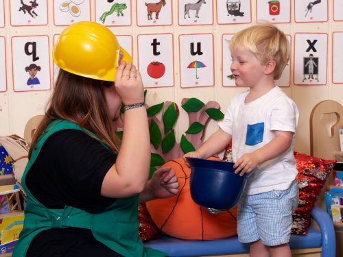 Young boy playing with his key person in the Toddlers room at Juniors Day Nursery.