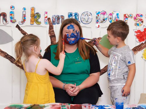 Children painting the face of their key person in the Toddlers room at Juniors Day Nursery.