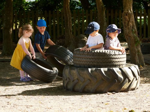 Toddlers playing outside with the tractor tyres at Juniors Day Nursery.