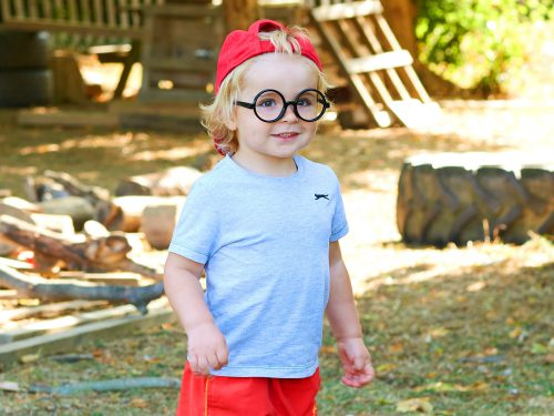 Cheeky boy in round rimmed glasses playing outside at Juniors Day Nursery.