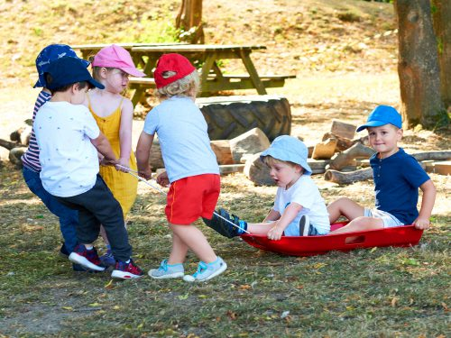 Children playing outside with a plastic sledge in the garden at Juniors Day Nursery.