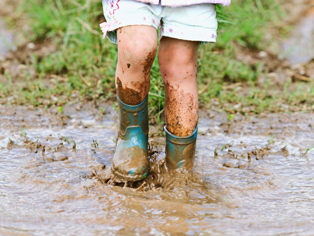 Preschool boy in wellies playing in muddy puddles at Juniors Day Nursery.