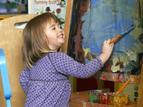 Cheeky young girl painting in the Toddlers room at Juniors Day Nursery.