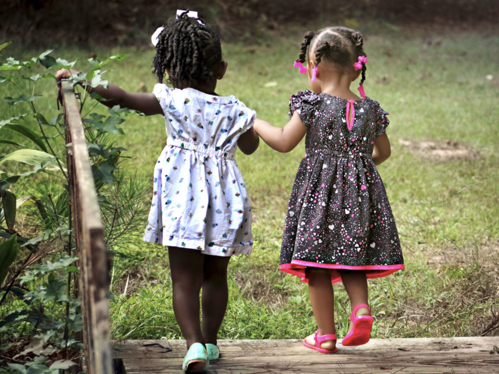 Two girls exploring the garden at Juniors Day Nursery.